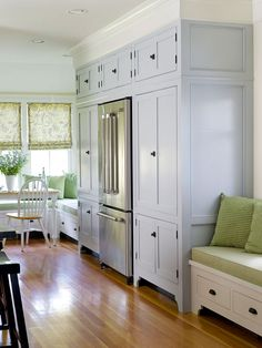 Cabinetry surrounding the stainless-steel French-door refrigerator offers storage for both the kitchen and the adjoining breakfast nook.