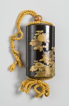 Inro with design of chrysanthemums and rocks. Gold and silver maki-e on black lacquer.