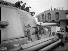 Royal Marines remove old paint from X gun turret on board HMS Rodney.