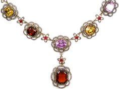 19th century gem and diamond cluster necklace set with diamonds, rubies, garnets, white sapphires, aquamarines, yellow zircons, pink topaz, peridot, tourmaline, and orange topaz. Via Diamonds in the Library.