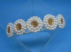 Tiara forrada com fita de cetim e 5 enfeites bordados de contas de pérolas brancas e miolo de chaton dourado.