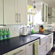 Love bright roman shade on window above sink.  Farmhouse sink.  Pendant Light.  White cabinets, different hardware, dark countertop.  LOOK AT THIS BLOG!  Cape 27 House Tour