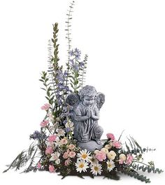 Angel with Pastel Flowers - Ray Hunter Florist & Garden. What could be more comforting than a lovely angel watching over a glorious arrangement of pastel flowers? The angel staute will inspire as a thoughtful reminder of your sincere sentiments.  Angel and Cherub statues may vary from picture. Other figures are available. Call or email us for current availability.
