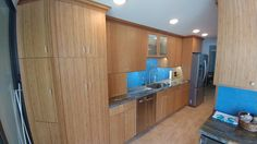 Beautiful Bamboo kitchen cabinets by DeWils, Marina Blue Quartzite counter tops and blue glass subway tile back splash are so warm and soothing in this Gulf front Corner Penthouse. Angled broom closet and pantry match the column we also wrapped in bamboo .