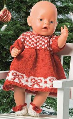 Dukkens fine julekjole har mønsterbort med sløjfer forneden på skørtet. På fødderne de kæreste små sko med sløjfepynt