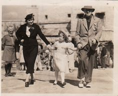 """Shirley Temple with John Ford and Phyllis Schuyler Thaxter on the set of """"Wee Willie Winkie,"""" 1937."""