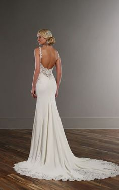 This designer sheath wedding dress from Martina Liana boasts graphic lace appliques with pearl and Diamante embellishments and illusion-lace sides and back. The Bellagio crepe skirt features gorgeous lace detailing and beading on its chapel train. The back zips up with ease under pearl beading