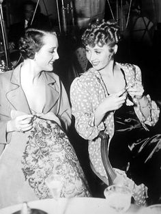 """Mary Astor stitches while Joan Blondell knits on the set of """"There's Always a Woman"""", 1938."""