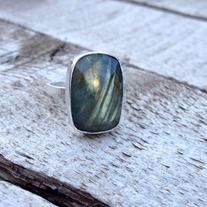 A stunning cushion cut or cube cut rectangle labradorite has been set in sterling silver. This rose cut on the labradorite helps bring out all the different hues of the stone: yellow, green, gold, blue, and grey accent lines. The ring band is made from sterling silver square cut wire. The stone i...