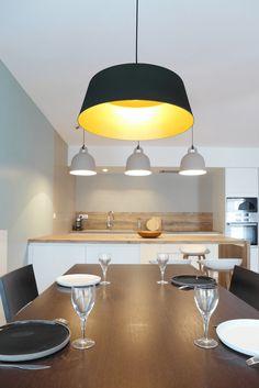 La salle à manger est séparée du reste de la pièce par une bibliothèque en bois coloris chêne naturel. Le rythme de cette étagère sur mesure lui donne une touche originale. La suspension noire et or est assortie à la table en bois foncé coloris wenge. Au loin, la cuisine en blanc et bois.
