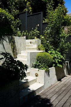 The modern architectural hardscaping in the garden is a perfect contrast to the traditional green and white plantings. A matte-black trellis backs romantic roses; fruit trees and geometric boxwoods sit in the Brutalist concrete planters. The balance of formal and modern mirrors the mix in the classical Tudor-style home | archdigest.com