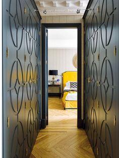 Un vestidor en forma de pasillo y con armarios de DM lacado y labrado.