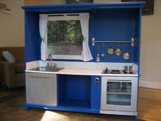 Old entertainment center turned into a play kitchen. The stove and dishwasher are stainless steal paint. Make the curtains. Picture of an outdoor where the TV goes. Sutton Grace: a repurposed play kitchen. Under $40