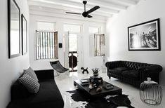 Salon noir et blanche, parquet peint en blanc, canapé noir, intérieur lumineux