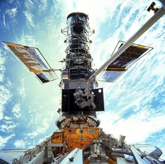 NASA astronauts John Grunsfeld and Steven Smith work to upgrade the Hubble Space Telescope during the STS-103 servicing mission to the observatory in December 1999. NASA has flown five servicing missions to repair and upgrade Hubble during its 25-year history.