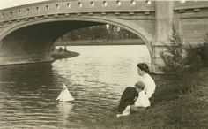 Woman and young boy watching model sailboat under bridge, Forest Park. (1910)