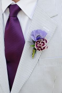 I love the suit color, but would change the tie to a dark navy, and add a tad bit bigger red boutonniere. I also love that they use 2 flowers within the boutonniere, I would want 1 small red flower, underneath a bit bigger red poppy flower.