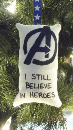 This Marvel-ous Avengers Logo pillow Christmas tree ornament features the stenciled Avengers logo with the quote I still believe in heroes, on