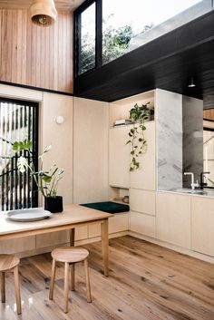 A wonderful mix of materials in this kitchen diner, from the wood flooring, panelled wood wall, white marble on the edge of the kitchen cupboards and black steel framed windows.