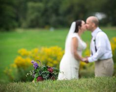 Bouquet of flower with the bride & groom kissing in the background.  Copyright Photographics Solution 2013