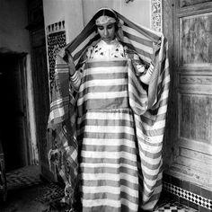 - Besancenot Jean (1902-1992) Citadine de Meknès en costume de circoncision. Elle porte le grand voile de soie, izar del hrir, rayé de bandes blanches et bleues sur la largeur et terminé par des franges filetées longues. Démonstration du drapé, troisième temps. Le reste du voile est ramené sur la tête après avoir fixé le côté gauche du tissu sur le devant à l'aide d'une petite fibule, bzim.- Arago