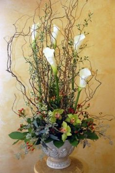Floral Arrangement with Curly Willow, White Calla Lilies, Green Orchids, Kangaroo Paw and Greenery http://www.busseysflorist.com/wedding-flowers/