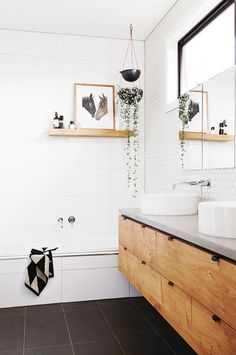 Bathroom with white honeycomb tile, a shower with a floating shelf styles with art and greenery, and a floating twin vanity sink