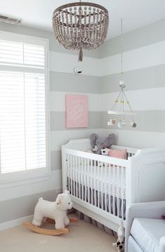 White and gray nursery features walls painted with gray stripes lined with a white French crib, PB Kids Ava Regency Crib, dressed in a gray ruffled crib skirt illuminated by a gray beaded chandelier, RH Baby & Child Dauphine Wood Pendant.