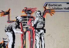 """Uma exposição dedicada às obras de Jean-Michel Basquiat entrará em cartaz no Barbican Centre de Londres e, nesta segunda (18), dois murais do artista de rua britânico Banksy apareceram no local. As duas obras juntaram o grafite neo-expressionista do americano com as famosas críticas sociais do britânico. Um dos murais faz referência a obra de Basquiat de 1982 """"Boy and Dog in a Johnnypump"""", mostrando um menino sendo revistado por policiais. Em sua conta oficial no Instagram, o enigmático…"""