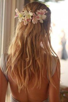 Semiraccolto mosso con fiori bianchi e rosa - I ciuffi laterali sono raccolti e tenuti fermi da una mini coroncina di fiori per questa acconciatura per capelli lunghi molto elegante.