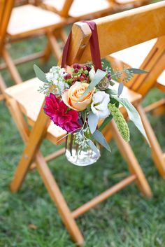 roses hanging in jar for outdoor wedding ceremony folding chair floral isle markers at Trump Winery wedding.