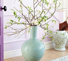 Place a tall vase full of quince blossoms on the floor to make the entry feel a bit like an interior garden.
