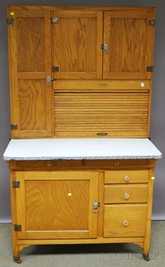 Sellers Oak Tambour Hoosier Cabinet, Indiana, the interior with tin and metal fittings and accessories including sifter, milk glass shakers, white and granite enameled metal work top, in two parts, brass label, ht. 70, wd. 40 3/4, dp. 27 3/4 in.