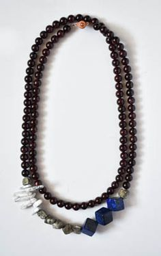 This Designs by s.e.K long garnet necklace features pyrite, lapis lazuli, and white marble stones with an asymmetrical style and an antique brass button clasp. This necklace can be worn long or doubled for a statement look.
