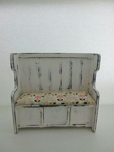 A12th scale dollhouse bench, the seat to this bench does lift up, This bench has been painted with a black undercoat and then painted over with a white furniture paint, it has then been sanded down to show the black underneath to give it a worn look, and then sealed with a matt
