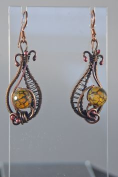 An open wire wrap weave is used on these patinaed copper earrings. The wire is first torched, and shaped into the paisley form. Then wire wrapping is done to fasten everything together. The 11 mm Drag