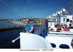 Helsingborg, Sweden - 06 May, 2018: Swedish man in Levis T-shirt poses for photo and passengers enjoy sun on upper dock Scandlines ferry boat cruising between Helsingborg Sweden and Helsingor Denmark