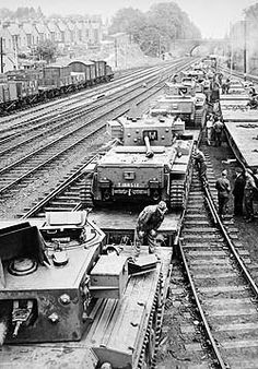 a black and white photograph of tanks loaded onto flatbed railway carriages