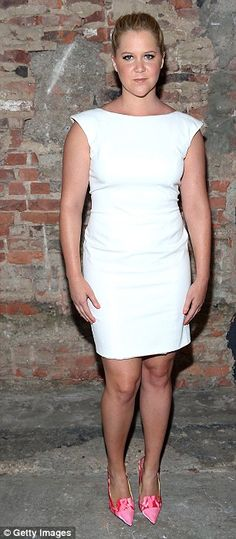 Comedian Amy Schumer wore a simple white dress with pink pumps for the Christian Siriano show at #NYFW http://dailym.ai/1tmeCGR