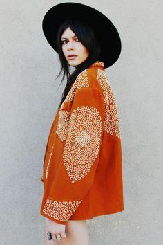 orange embroidered jacket and black hat