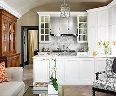 A small kitchen layered with elegant materials and sparkling accessories.