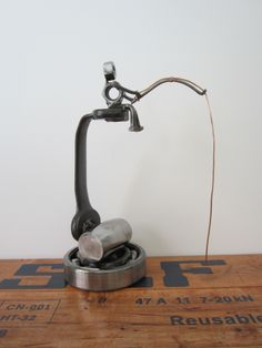 Fishing off the wrench. This FISHING NUT is a unique sculpture crafted from repurposed metal parts and mounted on a skf ball bearing. www.etsy.com/shop/sportsnuts