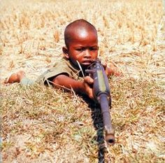 child soldier, if you can hold it you can shoot it, this boy looks around 7 years old not even, that rifle is bigger than him. this just shows you how bad people are to put a gun in these poor kids hands