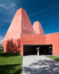This red concrete museum by Laureate Eduardo Souto de Moura has four wings and two pyramid-like chimneys.