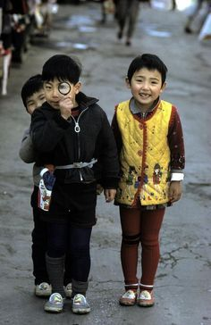 Three smiling Japanese kids with magnifying glass | Tokyo 1961 by Burt Glinn.