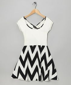 Designed with a white bodice, zigzag skirt and a stretchy fabric blend, this lithe slip-over dress is a showcase of comfort and jazzy style.