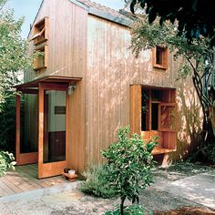 "In Oakland, California, two designers transformed a 100-year-old, 400-square-foot barn barn into cozy home of their own. Outside, the couple clad the house with a rain screen of 1.5-by-1.5-inch strips of spruce to create a ""modern rustic barn."" The extra-deep sills of the first-floor window become a bench on the outside and a shelf on the inside.  Photo by: Aya Brackett"