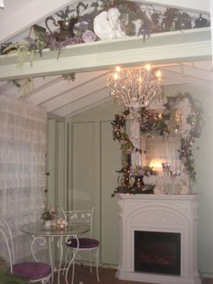 The inside of my she shed (Princess Palace). Done in purple, sage and white. With a fireplace, mirror, purple roses, chandelier, candles, cherubs and silver tea sets.