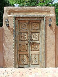 Adobe wall with carved wood garden door.  Southwestern style architecture. Santa Fe Door