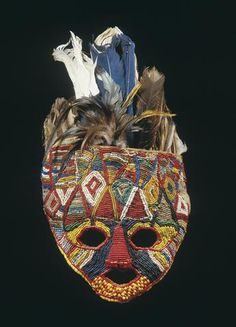 A Tabwa beaded facemask Democratic Republic of Congo, of classical form with fully beaded surface in geometric patterns. Feathers inserted to the top. An example with an appealing combination of colors. height 13in
